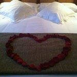 Pétalos de rosa en la cama.