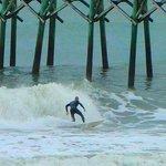 surfing next to pier