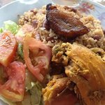 Braised chicken, rice and beans, tomato and lettuce salad with vinegar dressing, and plaintain s