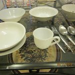 1 teacup, no saucer, 1 spoon, 1 small bread-plate, lots of bowls and some spoons & forks.