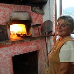La Mamma haciendo pizza en el horno de leña para la cena