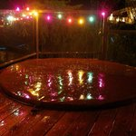 Holiday lights around hot tub on deck overlooking lake
