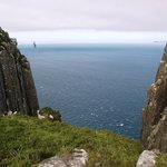 A slackliner between two of Fair Head's cliffs