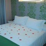 cama adornada con petalos de rosa y caamelos