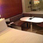 Bed, seating area and bathroom (Standard Queen Corner Room)