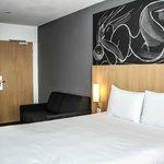 Chambre triple avec un grand lit et le sofa bed replié
