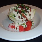 Our Classic Wedge Salad with a Maytag blue cheese dressing and Nueskie's Bacon