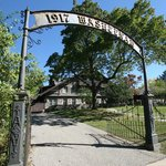 The large gate frames the historic bed and breakfast namesake building, Stone Chalet.