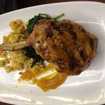 14oz Pork Chop grilled to perfection includes cornbread stuffing, sautéed spinach, finished with