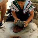 Local Ngobe woman demonstrating the traditional chocolate grinding process