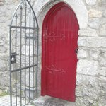 Arched Red Door with Wrough Iron Gate