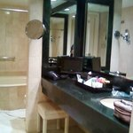 Bathroom with large vanity, double headed shower, wall magnifier mirror and tv