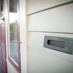 The house retains a number of original hardware features, such as this vintage mail slot.
