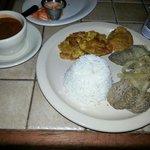 Biftec encebollado con arroz, habichuelas y tostones.