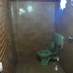 Bathroom of rock house, mold covered up with plastic sheeting