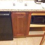 Kitchen area: mini fridge, microwave, coffee maker, glasses, cups, etc