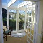 Looking from bedroom into conservatory with open doors