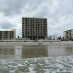 View of hotel (larger building) from beach during low tide