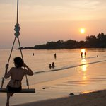 Many swings are hung along the beach, sunset