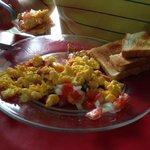 Huevo con tocino acompañado de salsa Mexicana.