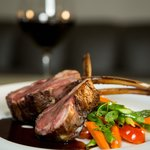 Colorado Rack of Lamb with whipped potatoes, sautéed vegetables, and mint jus.