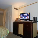 room with tv, coffee maker, and fridge