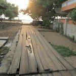 accès à l'hôtel sur l'égout pestilentiel du village recouvert des planches