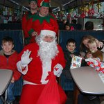 Santa and the elves welcome their guests with presents
