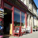 Shop frontage on Rothbury High Street in summer, Cragside tree-line beyond.