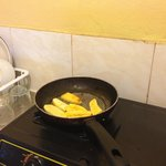 Making plantains on hot plate in kitchen