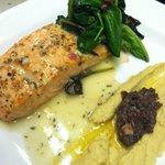 Atlantin Salmon hummus, tapenade, roasted garlic vinaigrette, and Lemon wilted greens.