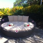 cute chair next to pool. Nice touches with flowers and towels.