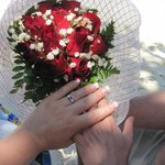 Joining Hands Showing Engagement Ring and Roses