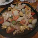 Sizzling hot plate of seafood and vegetables.