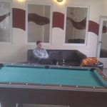 A Pool table, a cool dude and a smoking room.