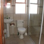 Shared bathroom with walk in shower and seating area