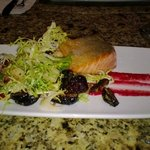 Salmon with a small date salad garnish.
