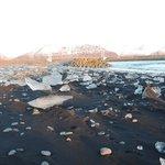 Black sand beach with bits of icebergs