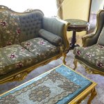 Gilt and upholstered chairs, and sequinned table mat on marble-topped coffee table!