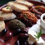 Platter of confit garlic with local feta, olives and dips