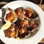 Tasty baked oysters topped with cheese and a small crab cake.