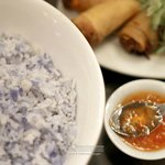 Rice colored and scented with bungah telang, spring rolls in the background.