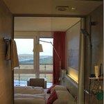 Blick aus dem Bad durch die gläserne Dusche ins Zimmer