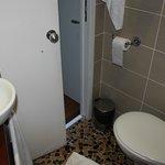 SDB, douche (sans rideau) et toilettes dans un espace très réduit,