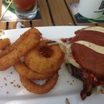 burger with pretzel roll and onion rings