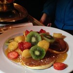 Breakfast: pancakes with fried bananas and fresh fruit, topped with caramel sauce.