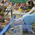 A guest gets a pedicure on the crowded sands of Boca Chica