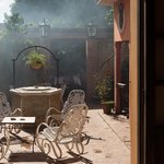 The barbeque in action, lunch in the arbour visible beyond the chairs, or dinner in the courtyar