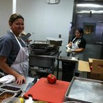 Two ladies working in the smaller kitchen.