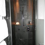 trendy shower cubicle showing black marble and waterfall shower